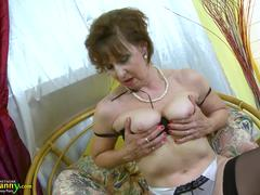 A granny in sexy lingerie is teasing and showing her body on the chair
