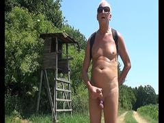 A grandpa is jerking off his manhood outdoors