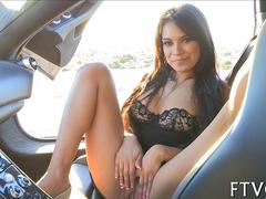 Enticing brunette spreading her pussy in a car and rubbing clit