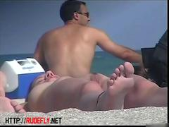 Naked chick on the beach sitting with her arms over her legs porno
